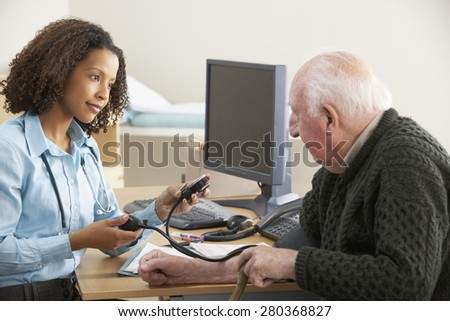 Young female Doctor taking senior man's blood pressure - stock photo