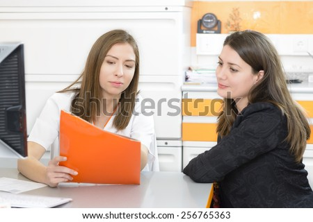 Young female doctor talking to a patient at clinic - stock photo