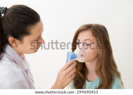 Young Female Doctor Using Inhaler Mask On Girl - stock photo