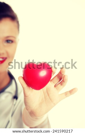 Young female doctor with heart in her hand. - stock photo