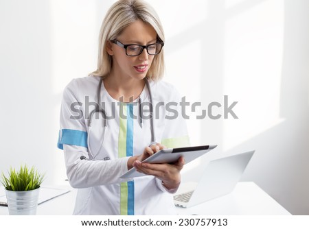 Young female doctor working with tablet computer - stock photo