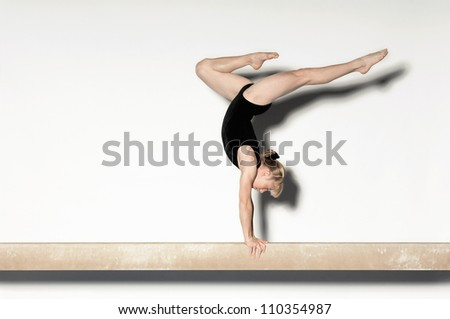 Young female doing a handstand on balance beam - stock photo