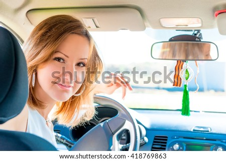Young female driver behind the wheel a car - stock photo