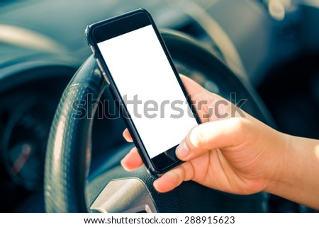 Young female driver using touch screen smartphone and gps navigation in a car. - stock photo