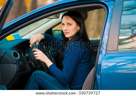 Young female driving happy about her new car or drivers license. - stock photo