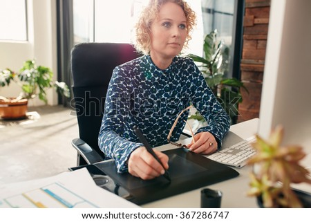Young female editor using graphics tablet to do work at her desk in the office. Professional graphic designer at work. - stock photo