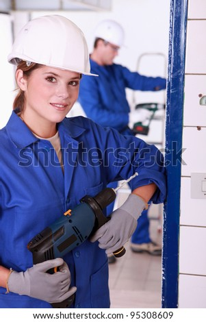 Young female electrician with a power drill - stock photo