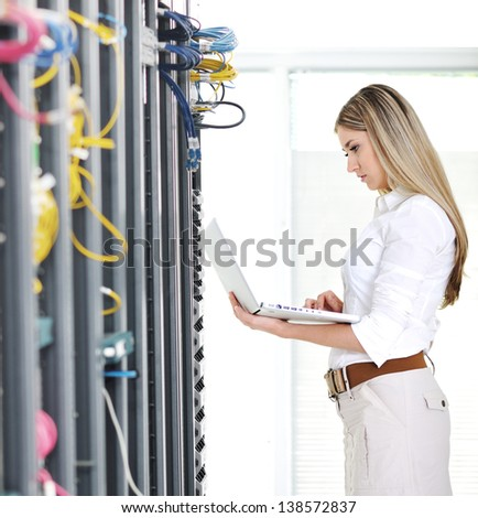 Young female engineer businesswoman with modern laptop in network server room - stock photo