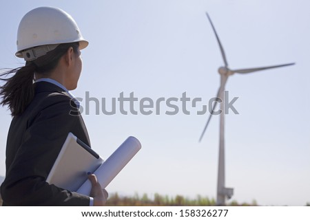 Young female engineer holding blueprints and checking wind turbines  - stock photo