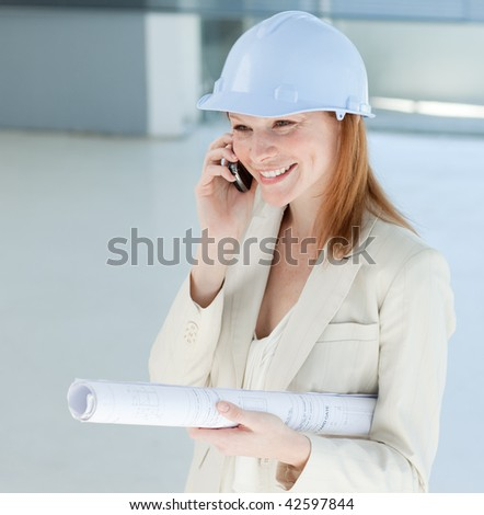 Young female engineer on phone carrying blueprints - stock photo