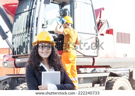young female engineer posing in junkyard with a worker - stock photo