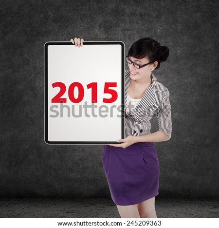 Young female entrepreneur holding a whiteboard with number 2015 - stock photo
