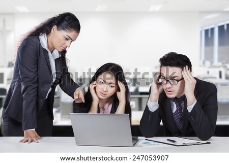 Young female entrepreneur pointing at the laptop to show the mistake of her subordinates - stock photo