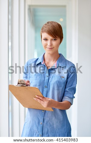 Young female entrepreneur smiling with a clipboard - stock photo