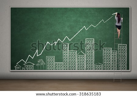 Young female entrepreneur using ladder to draw a real estate chart with arrow and building pictures on the chalkboard - stock photo