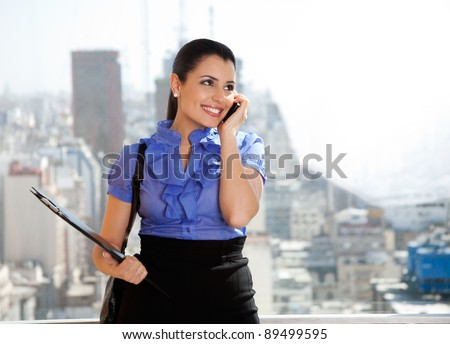 Young female executive talking on cell phone and looking away - stock photo