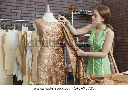 Young female fashion designer matching cloth with fabric draped on tailor's dummy - stock photo