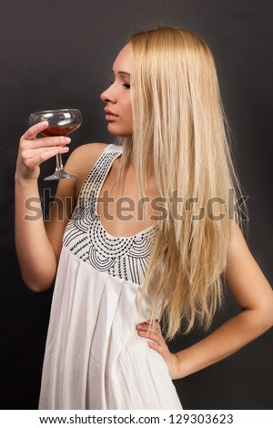 young female fashion model holding wine glass full of red wine - stock photo
