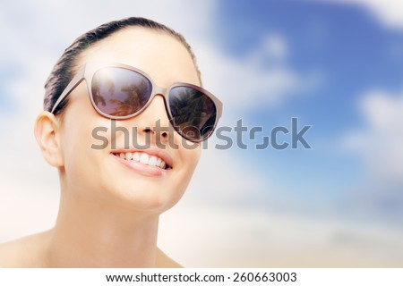 Young female fashion model smiling and wearing big sunglasses, sun protection and skincare concept - stock photo