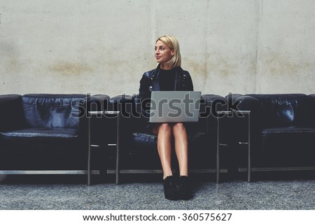 Young female freelancer in good mood dreaming about something while holding on knees open net-book, woman thinking about new ideas for creating design project while sitting with laptop computer  - stock photo