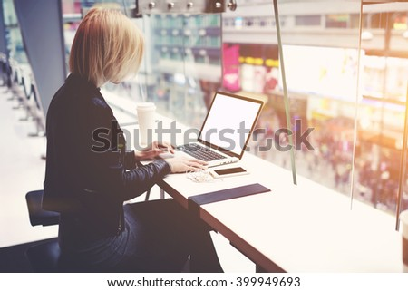 Young female freelancer is sitting in modern hipster cafe at the table with take away coffee, mobile phone and open laptop computer with blank empty copy space screen for your advertising text message - stock photo