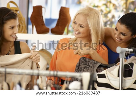 Young female friends shopping and searching among clothes at clothes store, smiling happy. - stock photo