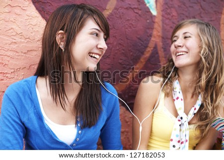 Young female friends smiling at each other while listening music together on earphones. Horizontal shot. - stock photo