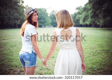 Young female friends walking together in the park.  - stock photo