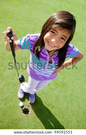 Young female golf player standing next to the hole - stock photo