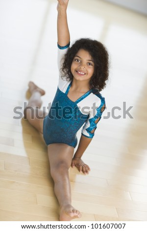 Young female gymnast doing split - stock photo