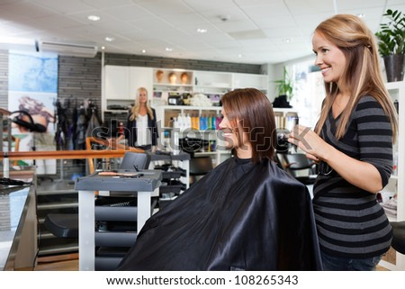 Young female hairdresser standing behind customer's chair after giving a haircut - stock photo