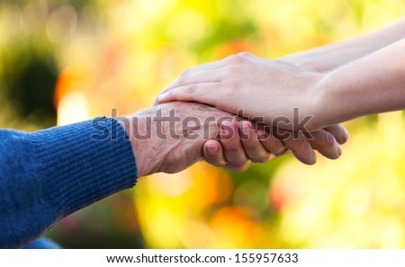 Young female hand holding an old man's hand. - stock photo