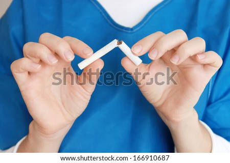 Young female hands holding a broken cigarette. Doctor's advice is to stop smoking. - stock photo