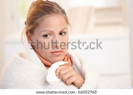 Young female having flu, feeling bad, wrapped up in blanket.? - stock photo