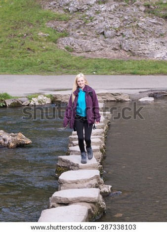 young female hiker crossing stepping stones in dovedale peak district - stock photo