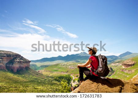 Young female hiker sitting on rock contemplating scenic view. - stock photo