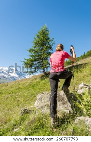 Young female hiker stretching on a rock. - stock photo