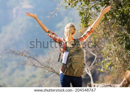 young female hiker with arms open on top of the mountain - stock photo