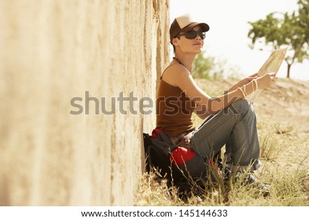 Young female hiker with map sitting by farmhouse - stock photo