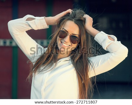 Young female hipster with glasses posing in front of a retro building, touching her hair. Shallow depth of field. Filtered version. - stock photo