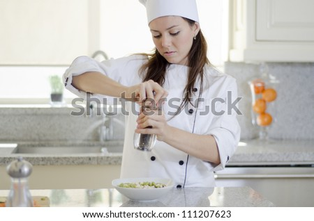 Young female hispanic chef adding some pepper to a dish - stock photo