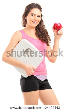 Young female holding an apple and a weight scale isolated on white background - stock photo