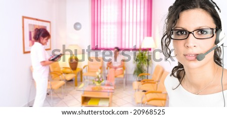 Young female hospital receptionist receiving phone calls in headset with clinic waiting room in background. - stock photo