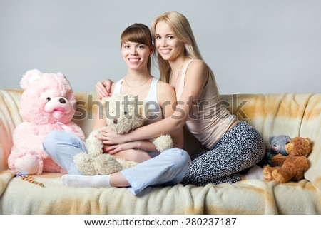Young female hugs her sister on the couch surrounded by plush to - stock photo