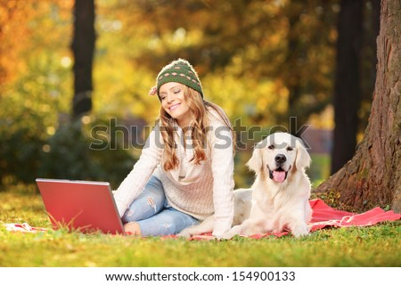 Young female in a park with her labrador retriever dog working on a laptop - stock photo