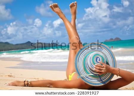Young female in beautiful summer hat enjoying sunny day on tropical beach. Summer luxury vacation. Holidays on Waimanalo Beach Park on the beautiful Hawaiian Island of Oahu - stock photo