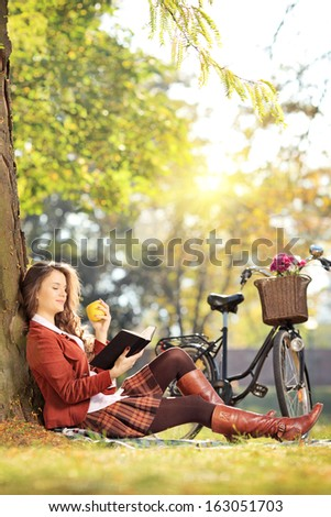 Young female in park reading a book and eating apple, on a sunny day - stock photo