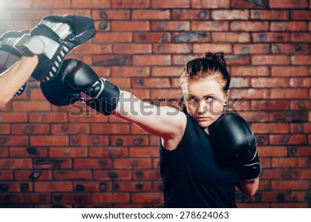 Young female in 20s boxing on a punching bag. - stock photo