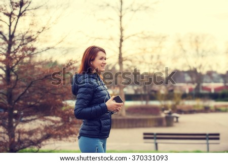Young female  in sports clothing enjoying music in park before a run.Beautiful young woman runner athlete with earphones during training in morning park. - stock photo