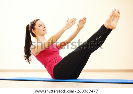 young female instructor doing stretching pilates exercises in sport club - stock photo